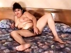 Fat Latina spreads her body across the bed and pleases her hairy twat